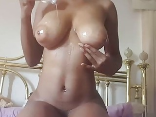 Riding her dildo and getting oiled up